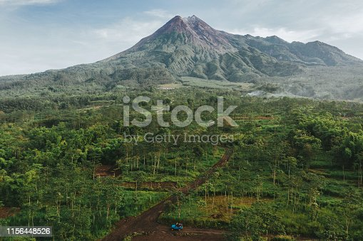 Scenic aerial view of old fashioned SUV driving through the jungles  on the background of Merapi volcano on Java, Indonesia