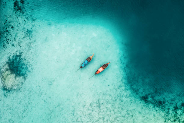 scenic aerial view of two boats on sea in thailand - thailandese foto e immagini stock
