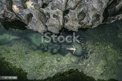 Scenic aerial view of young Caucasian  woman  floating on water in Angel's Billabong, Nusa Penida, Bali, Indonesia