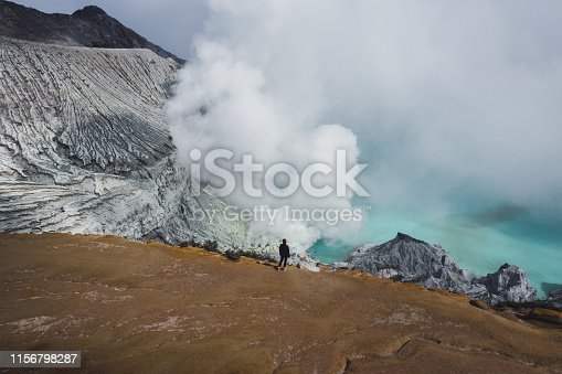 Scenic aerial view of young Caucasian woman  Ijen volcano on Java, Indonesia