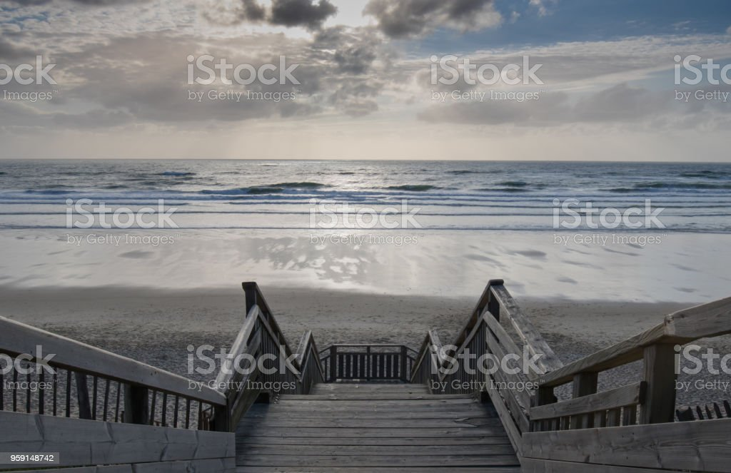 scenic biscarrosse beach in sunset with clouds and wooden footpath stairs, france stock photo