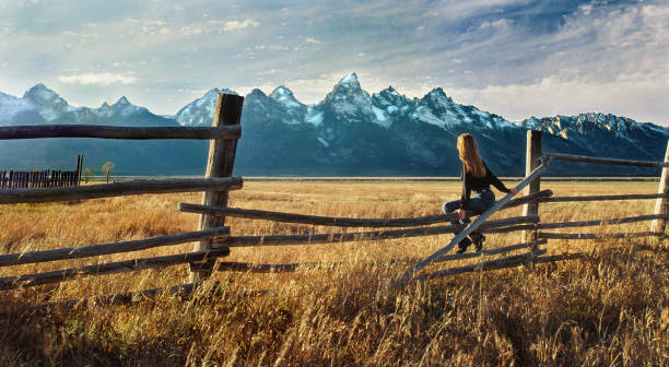 Scenic Color Portrait of Woman Sitting on Fence Looking at Grand Tetons stock photo