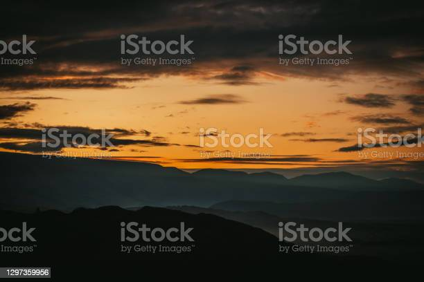 Photo of Scenic dawn mountain landscape with golden low clouds in valley among dark mountains silhouettes under sunset or sunrise sky. Vivid scenery with low clouds in mountain valley in illuminating color.