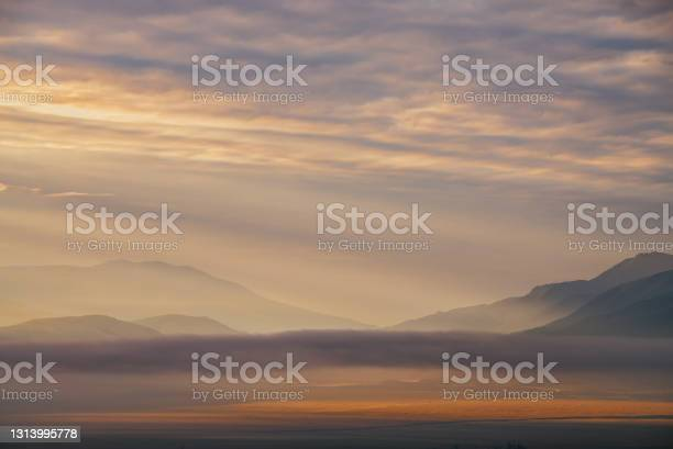 Photo of Scenic dawn mountain landscape with golden low clouds in valley among mountains silhouettes under cloudy sky. Vivid sunset or sunrise scenery with low clouds in mountain valley in illuminating color.