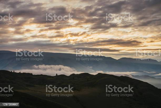Photo of Scenic dawn mountain landscape with low clouds among mountains silhouettes under orange sunset or sunrise sky. Vivid scenery with low clouds and trees on hill in illuminating color. Golden sundown.