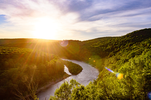 This is a photograph of the Delaware River winding through the Catskill Mountains and creating a natural state line between New York and Pennsylvania. The setting sun shines across the water and treetops in summer.