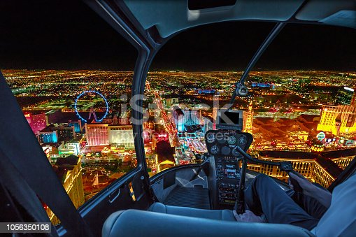 Helicopter interior on Las Vegas buildings and skyscrapers of downtown with illuminated casino hotels at night. Scenic flight above Vegas skyline by night in the Nevada United States of America.