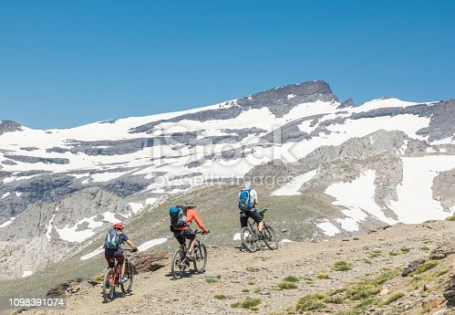 Three mountainbikers are riding upühill 2,000 metres (6,562 ft) above sea level in a row on a gravel road in the scenery landscape of the Andalusian Sierra Nevada which is a mountain range in the province of Granada and, a little further, Málaga and Almería in Spain. It contains the highest point of continental Spain and the third highest in Europe after the Caucasus Mountains and the Alps, Mulhacén at 3,479 metres (11,414 ft) above sea level. It is a popular tourist destination. Parts of the range have been included in the Sierra Nevada National Park. The range has also been declared a biosphere reserve. Canon EOS 5D Mark IV, 1/250, f/14, 105 mm.