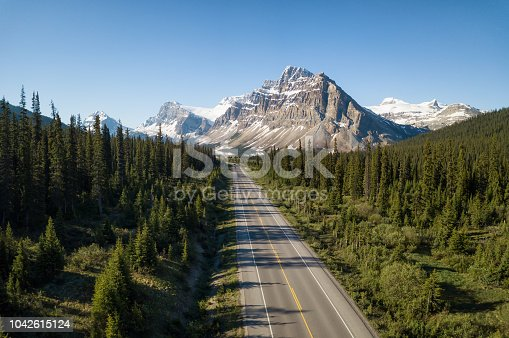 Aerial view of a scenic road in the Canadian Rockies during a vibrant sunny summer day. Taken in Icefields Parkway, Banff, Alberta, Canada.