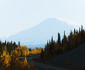 Scenic highway surrounded by mountains and trees in autumn season in Alaska
