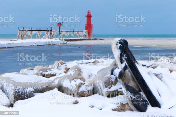 Photo of Scenic ice covered harbor with boat anchor after April blizzard