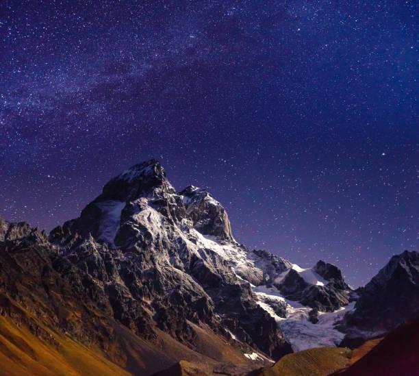 Scenic image of night sky over the peak Ushba. Location Mestia, Upper Svaneti, country Georgia, Europe. Main Caucasian ridge.