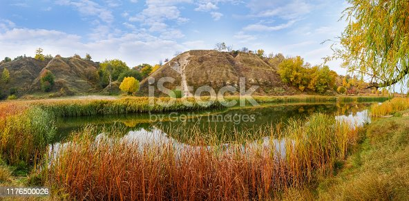Small scenic lake with shores overgrown with reed mace and phragmites at the foot of the hills in autumn day, panoramic view
