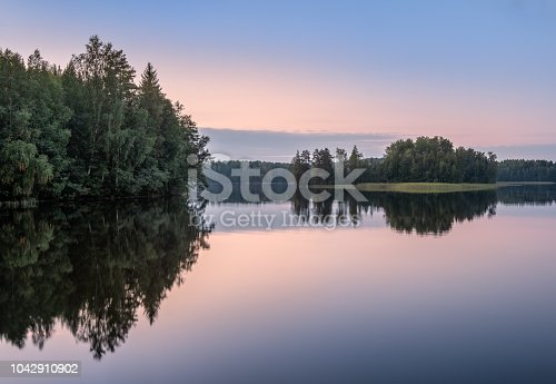 Scenic lake landscape with sunset and beautiful reflections at autumn evening in Finland.