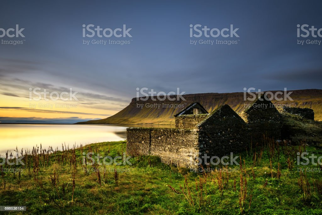 Schilderachtige landschap met inbegrip van verwoeste huis, typisch kliffen en een meer in IJsland royalty free stockfoto