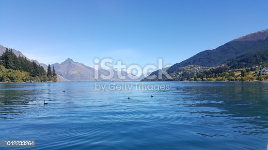 This is taken in Queenstown, New Zealand. The lake and sky are extremely blue. This is a famous tourist destination. A perfect place for recreation activities, relaxation and escape from work.