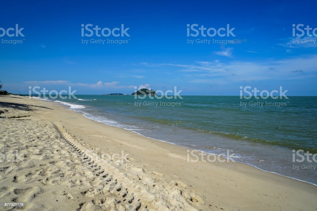 Scenic landscape of calm sea wave on white sandy beach with small islands and blue sky background stock photo