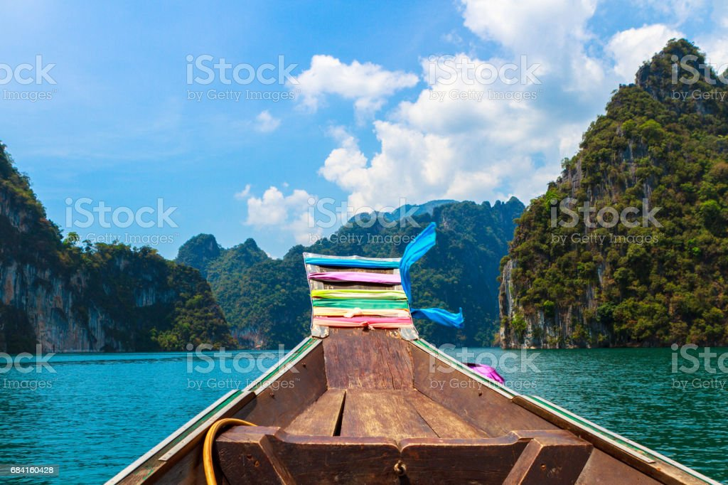 Scenic landscape of Cheo Lan lake in Thailand. Part of traditional thai longtail boat on foreground. Green mountains and dramatic sky on background. Selective focus on the boat. Travel Thailand royalty-free stock photo