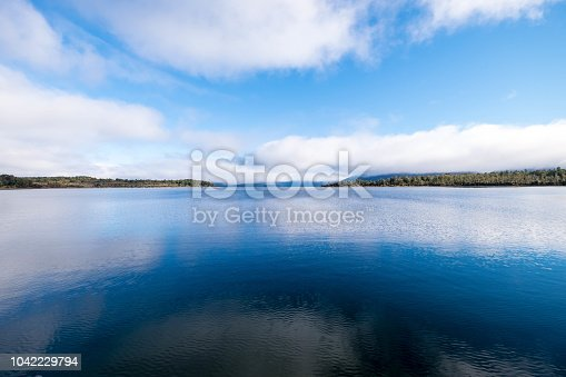 This is a photograph of a very blue lake. The water looks crystal clear. It has a perfect mirror image of the sky and trees.