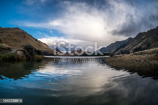 A simple background of a lake in New Zealand. The cloud formation looks interesting. One can see the water reflection of the clouds and mountains.
