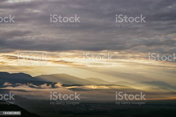 Photo of Scenic mountain landscape with golden low clouds above village among mountains silhouettes under dawn cloudy sky. Atmospheric alpine scenery of countryside in low clouds in sundown illuminating color.