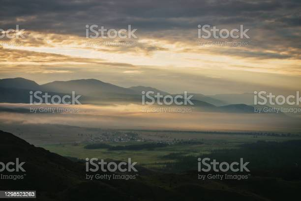 Photo of Scenic mountain landscape with golden low clouds above village in mountain valley among mountains silhouettes under dawn cloudy sky. Atmospheric alpine scenery of countryside in orange low clouds.