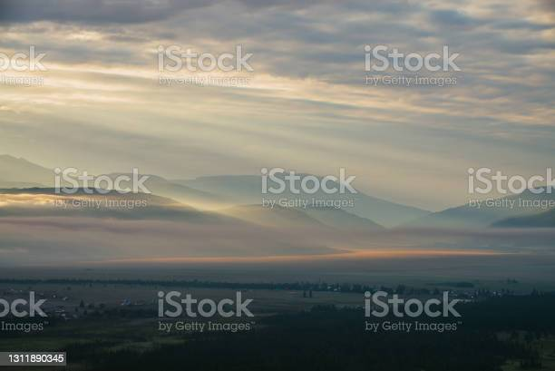 Photo of Scenic mountain landscape with orange lilac low clouds above village among mountains silhouettes under dawn cloudy sky. Atmospheric alpine scenery of countryside in low clouds in sundown golden color.
