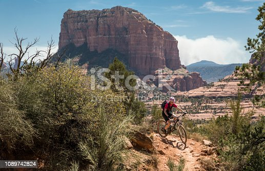 A female mountainbiker is riding on a flat rock area in front of scenic rock formations nearby the city of Sedona which is a city that straddles the county line between Coconino and Yavapai counties in the northern Verde Valley region of the U.S. state of Arizona. Sedona's main attraction is its array of red sandstone formations. The formations appear to glow in brilliant orange and red when illuminated by the rising or setting sun. The red rocks form a popular backdrop for many activities, ranging from spiritual pursuits to the hundreds of hiking and mountain biking trails. Canon EOS 5D Mark IV, 1/320, f/8, 70 mm.
