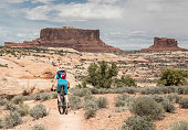 A lonely female mountainbiker is riding on the Ramblin Trail in the Navajo Rocks Trail Sytem (with Monitor and Merrimac buttes in the background) nearby Moab which is a city on the southwestern edge of Grand County in eastern Utah in the western United States. Moab attracts a large number of tourists every year, mostly visitors to the nearby Arches and Canyonlands national parks. The town is a popular base for mountain bikers who ride the extensive network of trails including the Slickrock Trail, and for off-roaders who come for the annual Moab Jeep Safari.\nCanon EOS 5D Mark IV, 1/320, f/13, 58 mm.