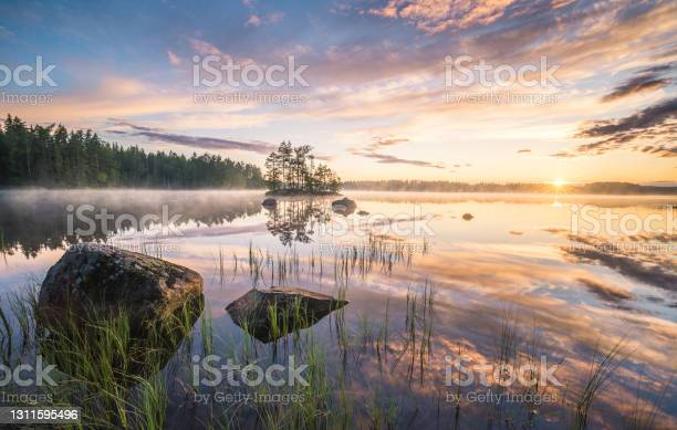 Photo of Scenic nature landscape with mood fog and beautiful sunrise at early summer morning in lakeside Finland