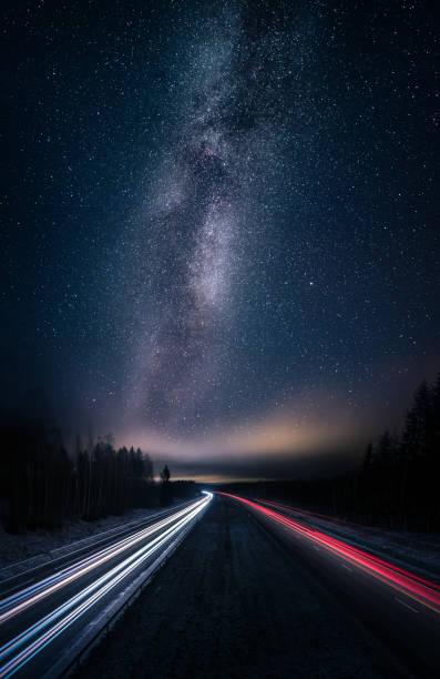malerische nachtlandschaft mit milchstraße und autobahn - weltraumaktivitäten stock-fotos und bilder