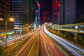 istock scenic of night light tail from car on the road with cityscape 1254171621