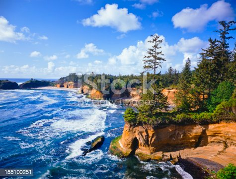 Waves of the Pacific Ocean crash against the sandstone cliffs of Whale Cove, Depoe Bay Oregon