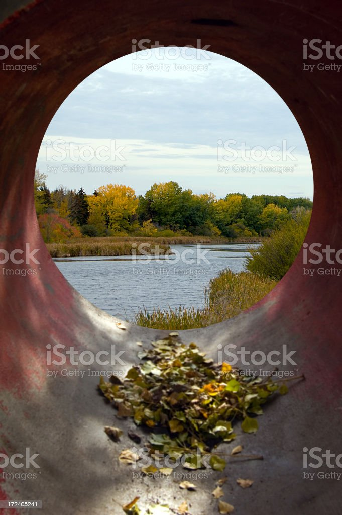 Scenic pond and green trees seen through a sewer culvert. royalty-free stock photo