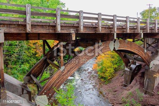 Timber bridge over scenic river in autumn