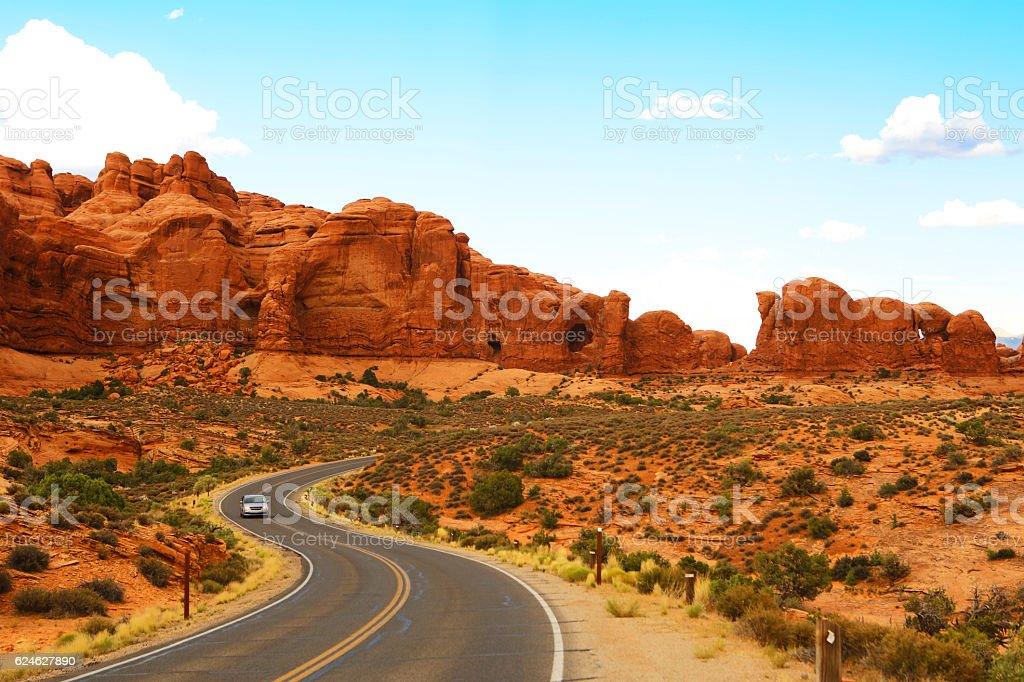 Scenic Road in Arches National Park Utah A single car driving on a scenic road at Arches National Park. Arches National Park Stock Photo