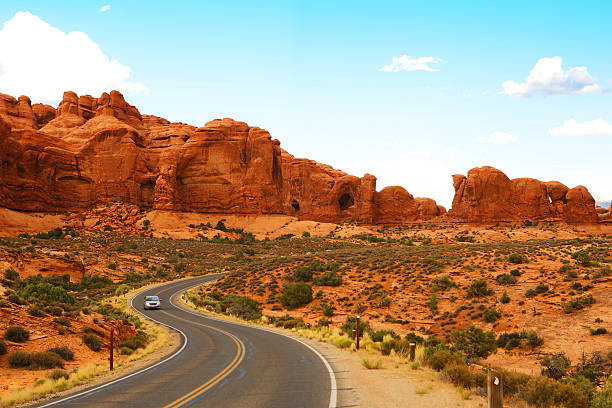 Scenic Road in Arches National Park Utah A single car driving on a scenic road at Arches National Park. arches national park stock pictures, royalty-free photos & images