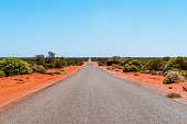 Remote asphalt highway in Australian bushland and the outback with red sand and shrubs