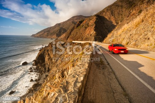 Car drives by the Pacific ocean rocky beach coast in California on the Cabrillo highway US 1