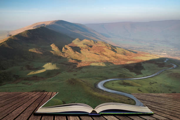 A scenic road winds its way through the Edale Valley on a foggy Winter sunrise in the Peak District in pages of open book, story telling concept stock photo