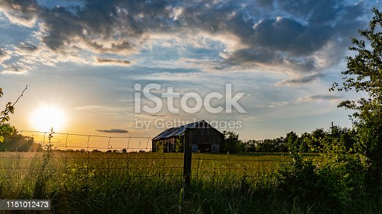 Rural countryside landscape of an old barn in a hay field with the sun to the left and a hog-wire fence in the foreground.