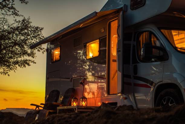 Scenic RV Camping Spot Scenic RV Camping Spot During Sunset. Class C Motorhome Camper Van. Travel Industry Theme. motor home stock pictures, royalty-free photos & images