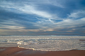 Scenic seascape. Empty sand beach and dramatic cloudy sky on background