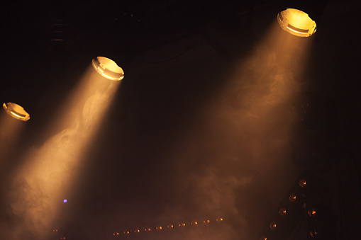 Scenic spot lights with bright beams in smoke, stage illumination