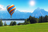 Scenic summer landscape with colorful hot air balloon flying above Alps mountains, lake and green field or meadow and forest in Bavaria, Germany, Central Europe