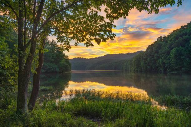 Scenic summer sunset over calm mountain lake stock photo