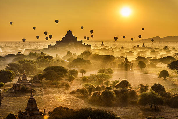 Scenic sunrise above Bagan in Myanmar Scenic sunrise with many hot air balloons above Bagan in Myanmar. Bagan is an ancient city with thousands of historic buddhist temples and stupas. myanmar stock pictures, royalty-free photos & images