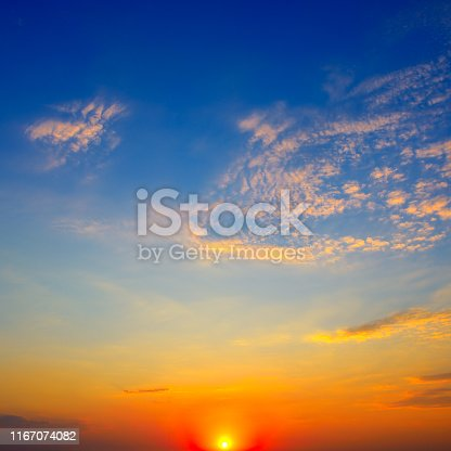 Scenic sunset on background bright blue sky and orange clouds