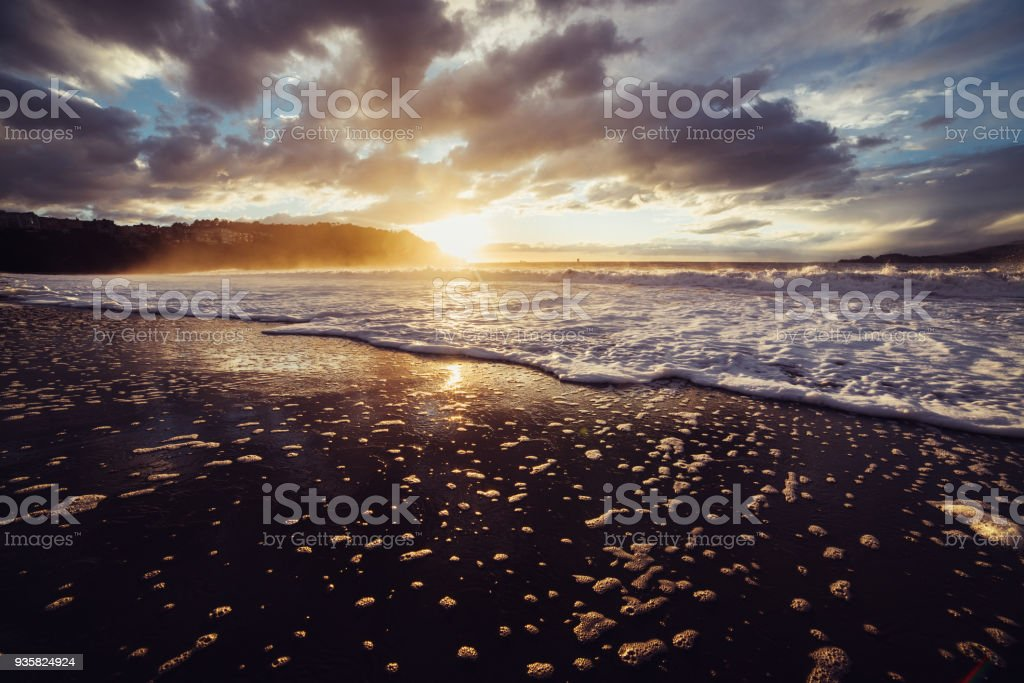 Scenic sunset on the ocean beach at at summer day and fog fro the water waves against cloudy sky. stock photo