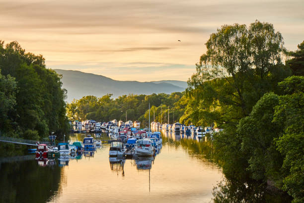 Scenic sunset view of Balloch harbour near Loch Lomond with floating boats reflected in river Leven, Scotland, United Kingdom. stock photo